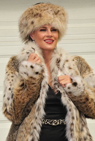 chearful: An attractive eastern European woman wearing a fashionable fur coat and fur hat Stock Photo