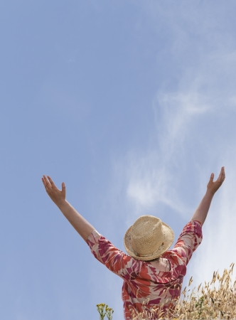Woman with hands raised toward heaven on the field with grass photo