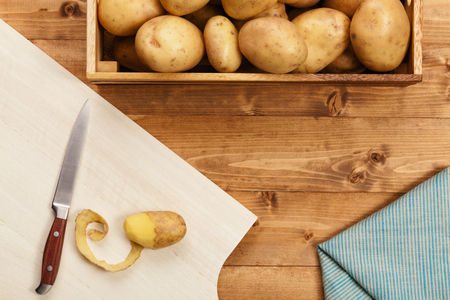Potato and knife on the chopping board