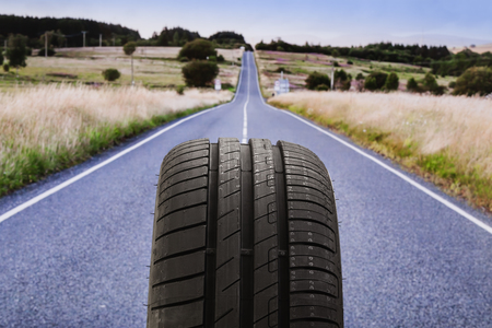 tyre tread: Tyre with street in background Stock Photo