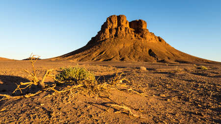 Sunset on lonely rocky sahara desert mountain in Morocco