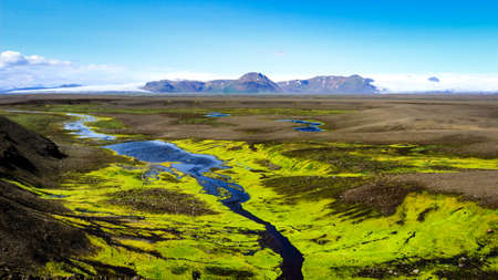 Icelandic landscape with glacier distinct mountains, mossy foreground and small river in green valley Stock Photo