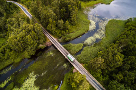 RV from above cruising over bridge over swedish waterscape drone aerial shot