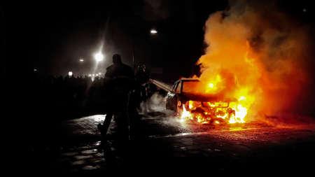 Firemen extinguishing flames of a burning car Banco de Imagens