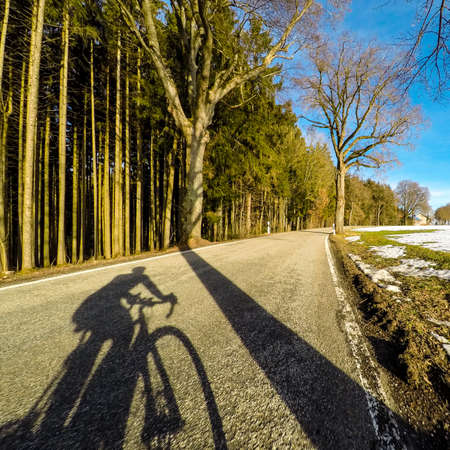 Cyclist shadow on winter road blue sky snow forest road bike