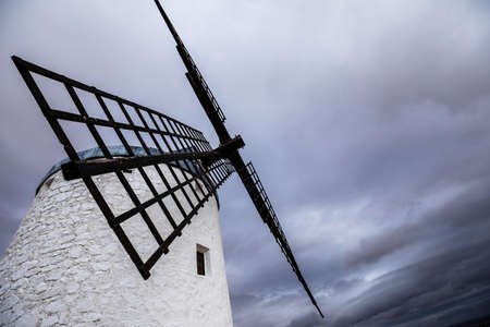 Restored old windmill in Spain blue sky white clouds picture taken from below Фото со стока