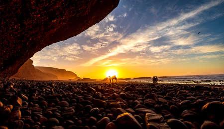 Sunset on Legzira Beach Atlantic Ocean Morocco Stone Bridge Camel Dromedar in the Sun