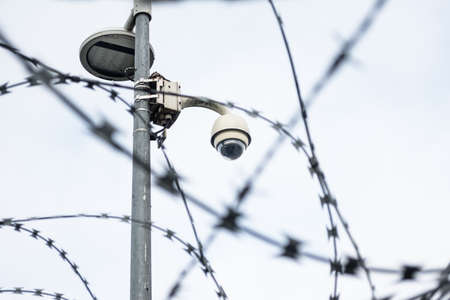 Barbed wire fence with surveillance camera prison security Archivio Fotografico