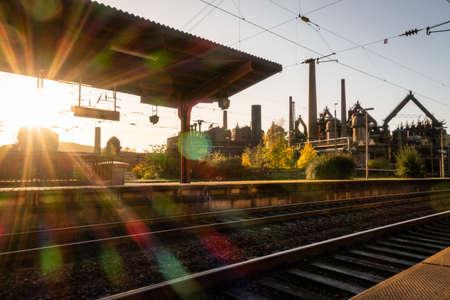 Railway station of german city Voelklingen with blinding sunlight star Archivio Fotografico