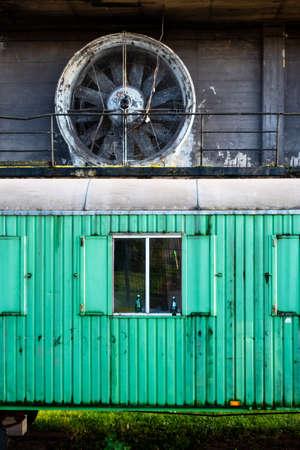 Green train car waggon cut-out beneath turbine propeller