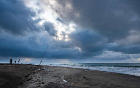 Fishing men below a stormy sky in the south of France Archivio Fotografico
