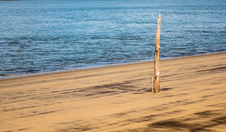 Wooden post on a sandy beach calm sea nothing else Archivio Fotografico