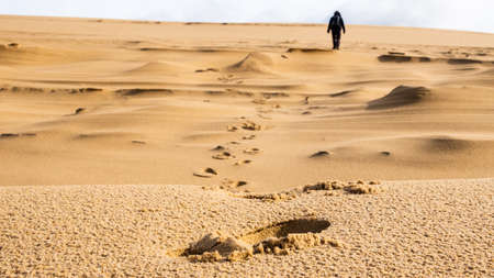 Silhouette of a woman walking away from the photographer on the dune du pilat in the south of france with footstep imprints in the sand