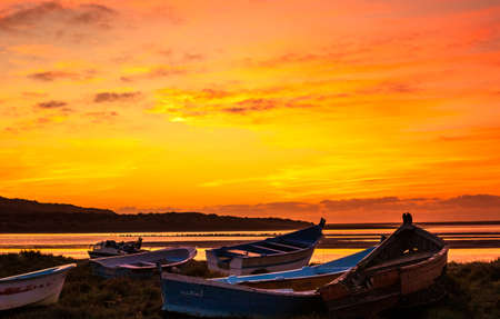 Fishing boats on marina ground below an amazing sunset in Morocco