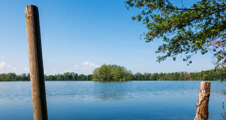 Wooden posts in front of a blue bavarian lake with small woodland island