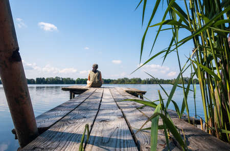 One woman sitting at the end of a weathered wooden jetty over a calm lake in bright daylight Bavaria