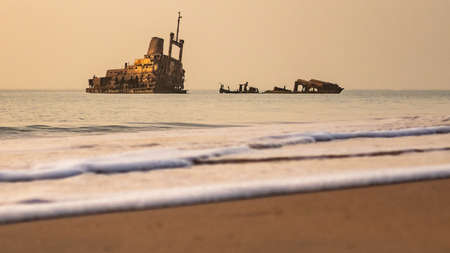 Beach Sunset with abandoned shipwreck hazy sky little surf