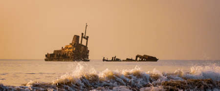 Beach Sunset with abandoned shipwreck hazy sky surf and spray of waves Archivio Fotografico
