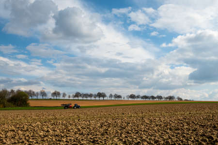 Tractor pulling a trailer of a plowed agricultural field with treelined road dramatic sky