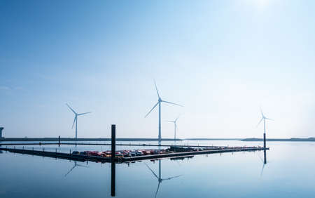 Small marina off the coast of the Netherlands with wind turbines in the background Archivio Fotografico