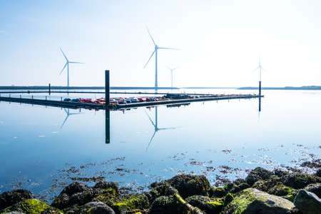 Small marina off the coast of the Netherlands with wind turbines in the background 版權商用圖片