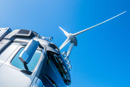 Silver colored  truck's driver cabin in front of a silver colored wind turbine propeller with blue cloudless sky