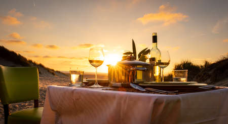 Honeymoon sunset candlelight dinner on the beach pot of mussels chair table sand dunes