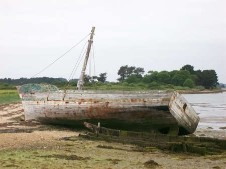 ship wreck: Shipwreck stranded on the bank of a river Stock Photo