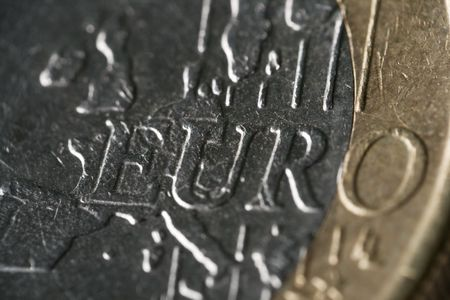 Extreme macro photo of a 1 Euro coin. The word ?Euro? is visible. Very shallow depth of field. Gold in color with silver inset.   NOTE: The extremely shallow depth of field was created by reversing a 50mm lens in front of a 100mm lens. The effect was achi Stock Photo