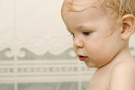 nude little girls: Young toddler takes a bath. Blond hair is wet. Looking down and left.