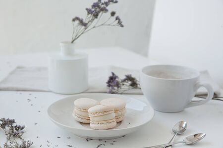 Macarons, morning coffee on light table with blurred vase and blue flowers on background Stok Fotoğraf