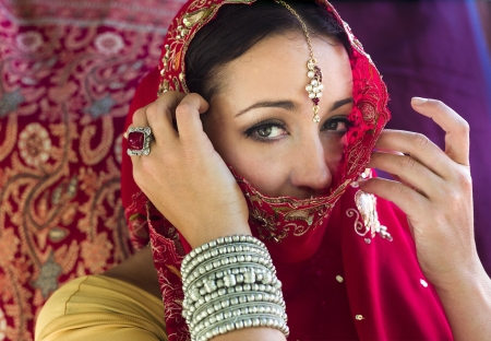Beautiful, mysterious woman in red Indian sari with traditional jewelry photo