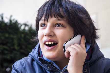 Teenage boy talking and laughing on cellphone photo