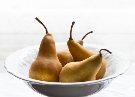 Golden pears in white porcelain bowl photo