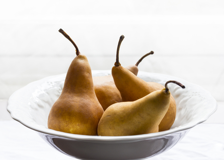 hardwoods: Golden pears in white porcelain bowl Stock Photo