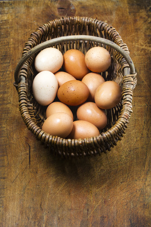 Basket of organic free range eggs on antique cutting board