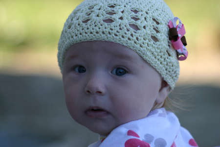 Baby girl wearing ivory hat with flower