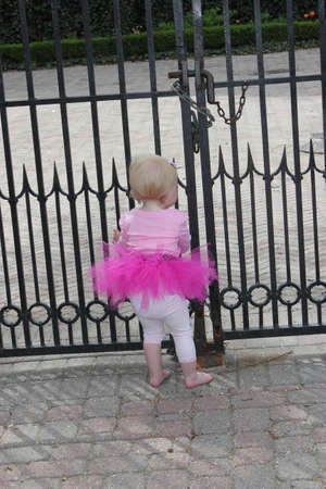 locked: Little girl in tutu infront of locked gate