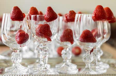 Strawberries decorate elegant crystal glasses Imagens