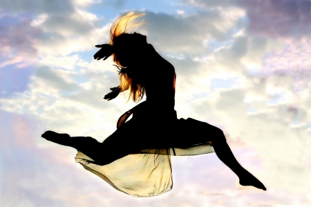 A young, attractive woman leaps through the air, with a beautiful cloudy sunset in the background.