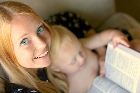 A young woman sitting on the couch, reading a book while her baby sits on her lap. photo
