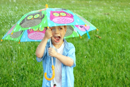 a young child is yelling as he holds a colorful umbrella in the rain. photo