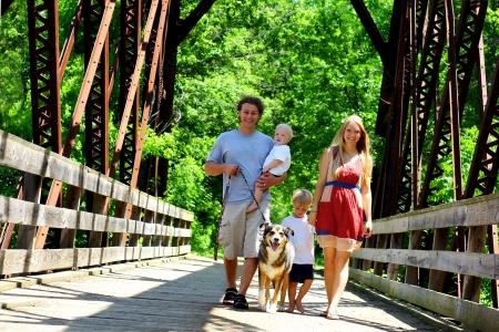 Een jonge, aantrekkelijke familie van vier personen lopen over een brug.