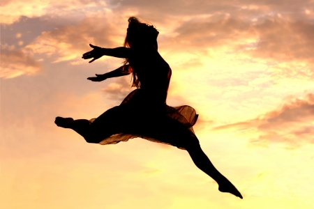 silhouette of a woman leaping through the air in front of a pink sunset photo