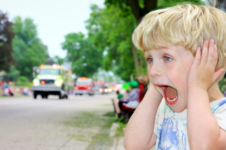 sirens: A young blonde boy covers his ears and looks excited as ambulances and fire trucks drive by in a parade.
