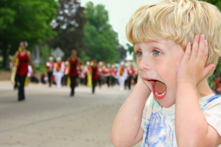 A cute toddler boy covers his ears as he watches a school marching band walk by in a parade.
