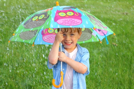 A cute little boy making a silly face while holding a colorful umbrella in the rain photo