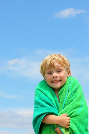 A very happy toddler boy wrapped in a beach towel in front of a summer sky photo