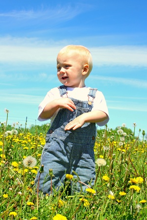 A happy baby boy clapping his hands while standing in a field of dandelions photo