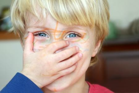 hand on mouth: Cute blonde toddler boy, covering his face with his hand.  His face is covered in marker.
